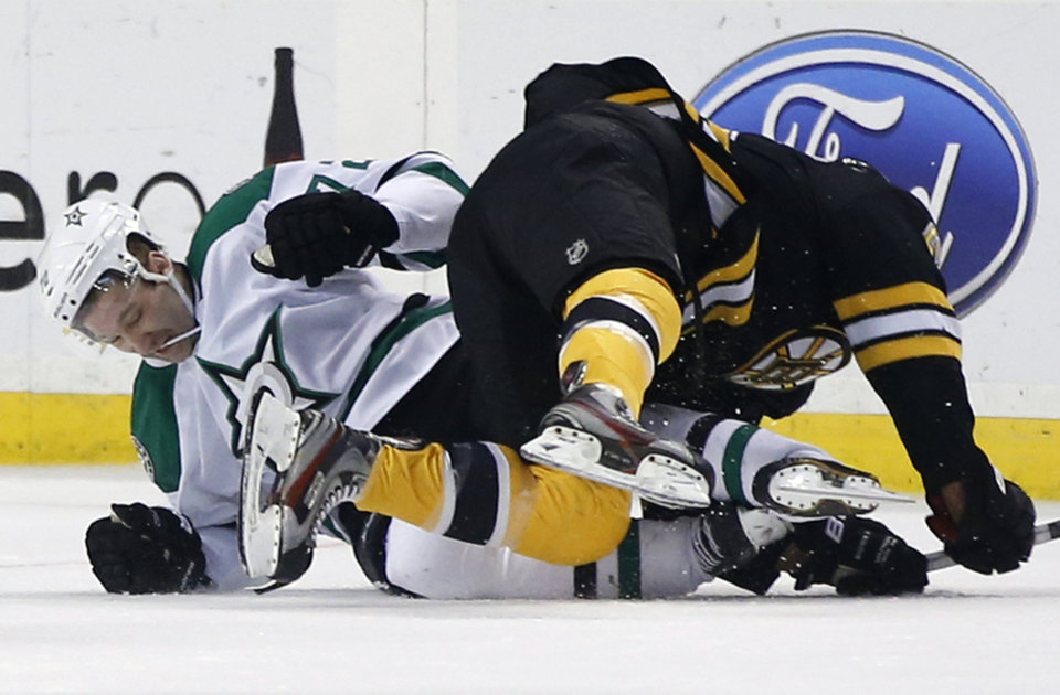Photo - Dallas Stars right wing Erik Cole, left, crashes to the ice with Boston Bruins defenseman Johnny Boychuk during the first period of an NHL hockey game in Boston on Tuesday, Nov. 5, 2013. (AP Photo/Elise Amendola)