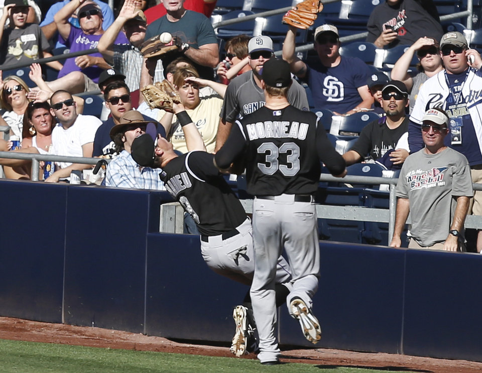 Photo - Colorado Rockies second baseman DJ LaMahieu crashes into the wall while catching a pop foul hit by San Diego Padres' Abraham Almonte in the fourth inning of a baseball game Wednesday, Aug. 13, 2014, in San Diego. (AP Photo/Lenny Ignelzi)