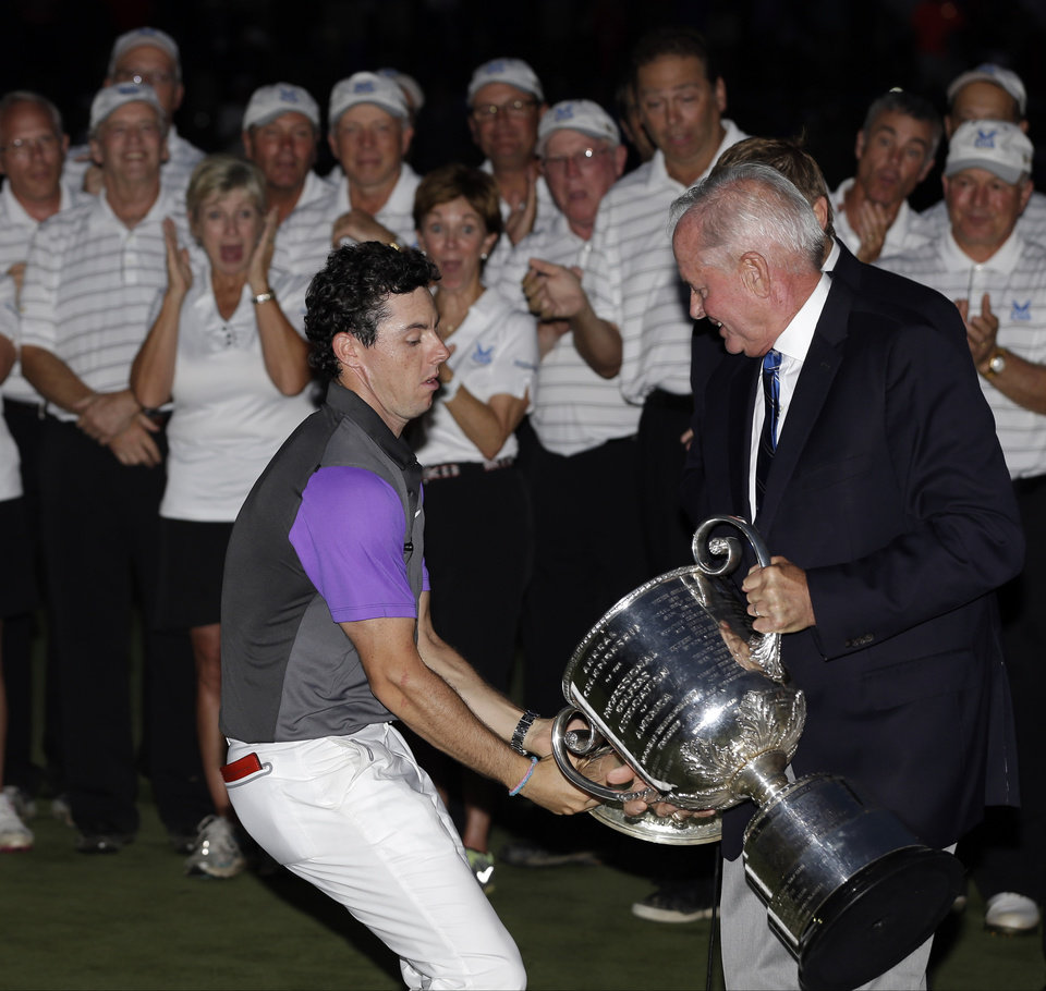 Photo - Rory McIlroy, of Northern Ireland, catches the Wanamaker Trophy from PGA of America president Ted Bishop after winning the PGA Championship golf tournament at Valhalla Golf Club on Sunday, Aug. 10, 2014, in Louisville, Ky. (AP Photo/David J. Phillip)