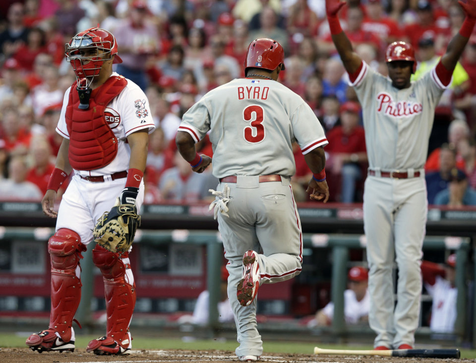 Photo - RETRANSMISSION TO CORRECT TO CORRECT NAME OF CATCHER - Philadelphia Phillies' Marlon Byrd (3) scores on a double by Domonic Brown in the fourth inning of a baseball game against the Cincinnati Reds, Friday, June 6, 2014, in Cincinnati. catcher Brayan Pena watches at left and John Mayberry Jr. celebrates at right. (AP Photo/Al Behrman)
