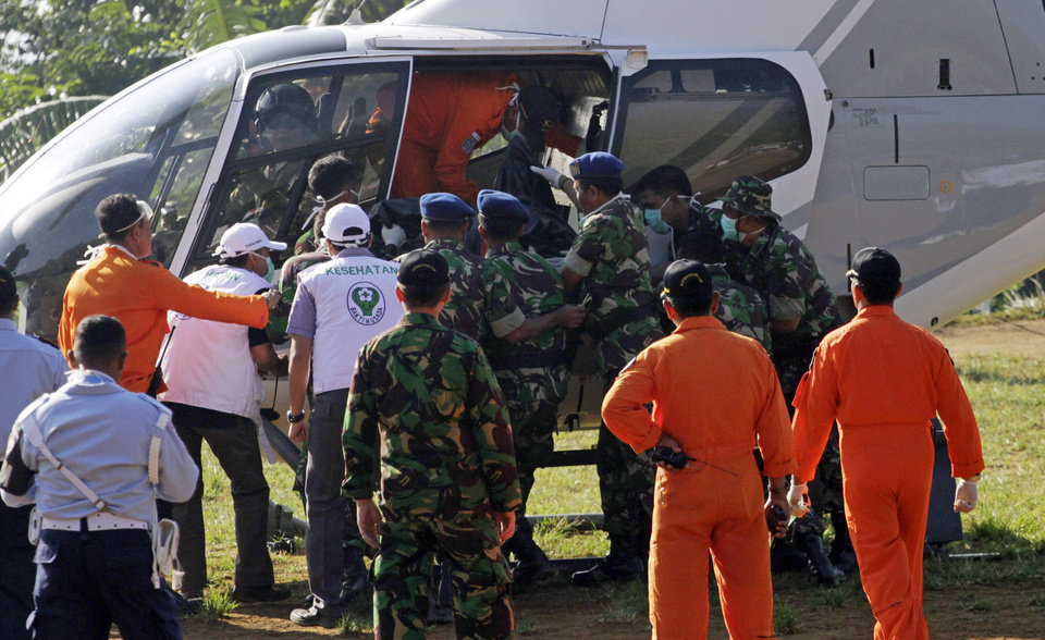 Photo -   Indonesian soldiers and rescuers load a victim of Wednesday's plane crash to a helicopter at Cijeruk in Bogor, West Java, Indonesia, Saturday, May 12, 2012. Search teams who scaled a volcano's steep slopes found at least 12 bodies Friday near the wreckage of the Russian-made Sukhoi Superjet-100 that crashed in Indonesia during a demonstration flight for potential buyers, an official said. All 45 aboard the jetliner that crashed Wednesday are feared dead.(AP Photo/Achmad Ibrahim)