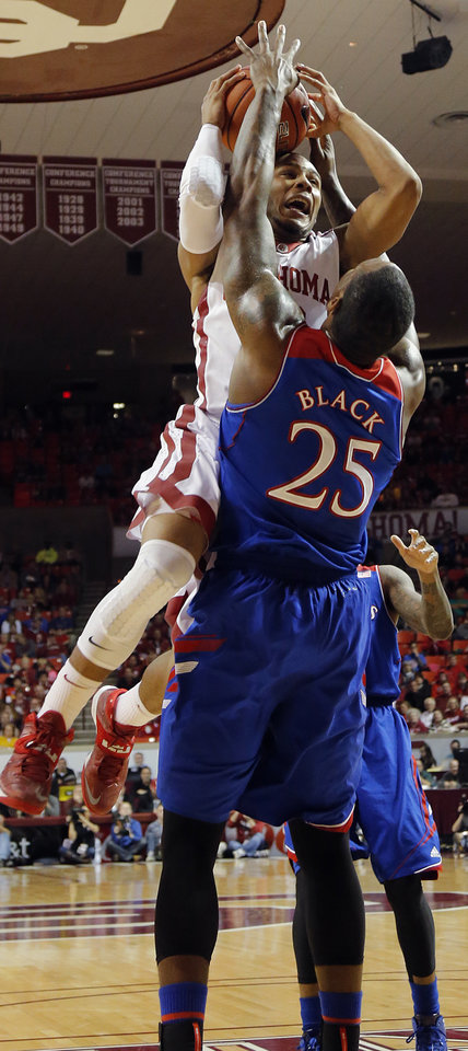 Photo - Oklahoma's Jordan Woodard (10) goes over the top of Kansas' Tarik Black (25) during the NCAA college basketball game between the University of Oklahoma Sooners (OU) and the University of Kansas (KU) Jayhawks at Lloyd Nobel Center in Norman,  Okla. on Wednesday, Jan. 8, 2014.   .Photo by Chris Landsberger, The Oklahoman