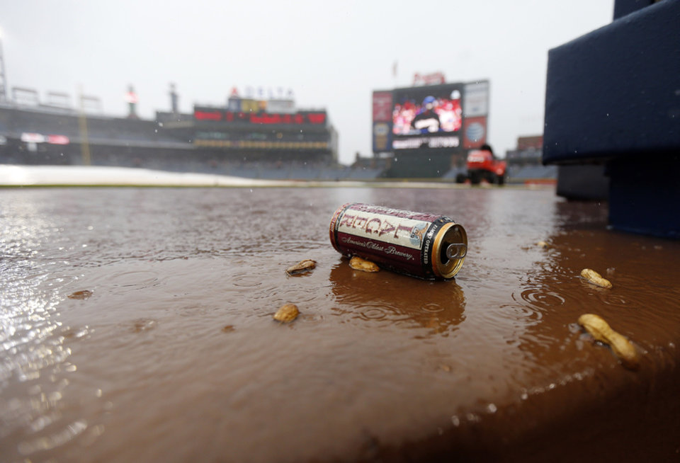 Photo - Debris washes into the Atlanta Braves dugout during a rain delay in the sixth inning of a baseball game against the Philadelphia Phillies in Atlanta, Sunday, July 20, 2014. (AP Photo/John Bazemore)