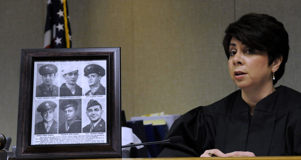 Judge Karen Khalil sits beside a framed photo of her six uncles that served in the military at Redford District Court (17th District) in Redford on Nov. 5, 2012. Veterans participate in special veterans court aimed at helping veterans who have been charged with drug and non-violent offenses. The specialized courts are a growing trend in courts across the country since Buffalo, N.Y. first started its vets court a few years ago. (AP Photo/The Detroit News, David Coates)