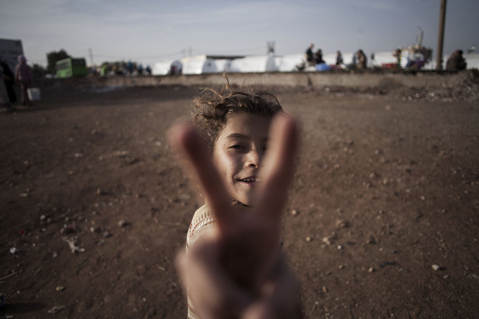 Photo -   A Syrian girl, who fled her home with her family due to fighting between government forces and rebels, flashes the victory sign at a refugee camp near the Turkish border, Azaz, Syria, Sunday, Oct. 7, 2012. (AP Photo/ Manu Brabo)