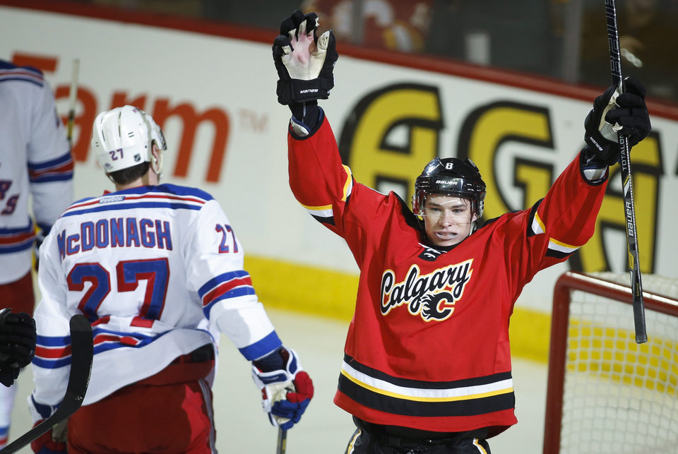 Photo - New York Rangers' Ryan Mcdonagh, left, skates away as Calgary Flames' Joe Colborne celebrates his goal during the first period of an NHL hockey game in Calgary, Alberta, Friday, March 28, 2014. (AP Photo/The Canadian Press, Jeff McIntosh)