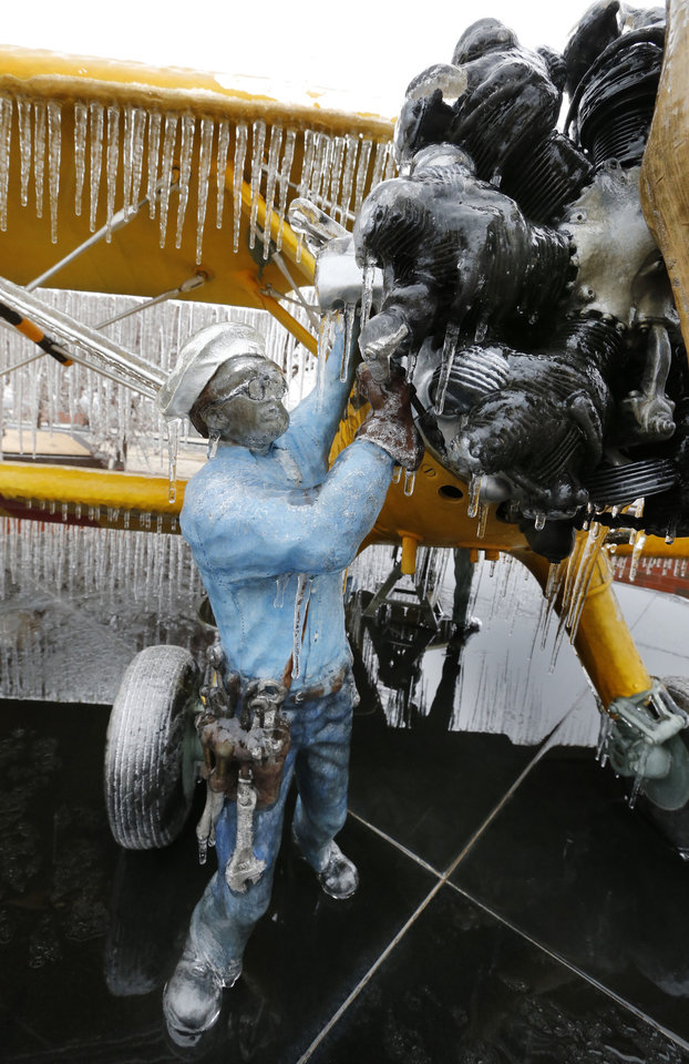 Photo - Ice covers a sculpture called the Yellow Peril near downtown after freezing rain covered everything with a thick layer of ice on Saturday, Dec. 21, 2013 in Norman, Okla.  Photo by Steve Sisney, The Oklahoman