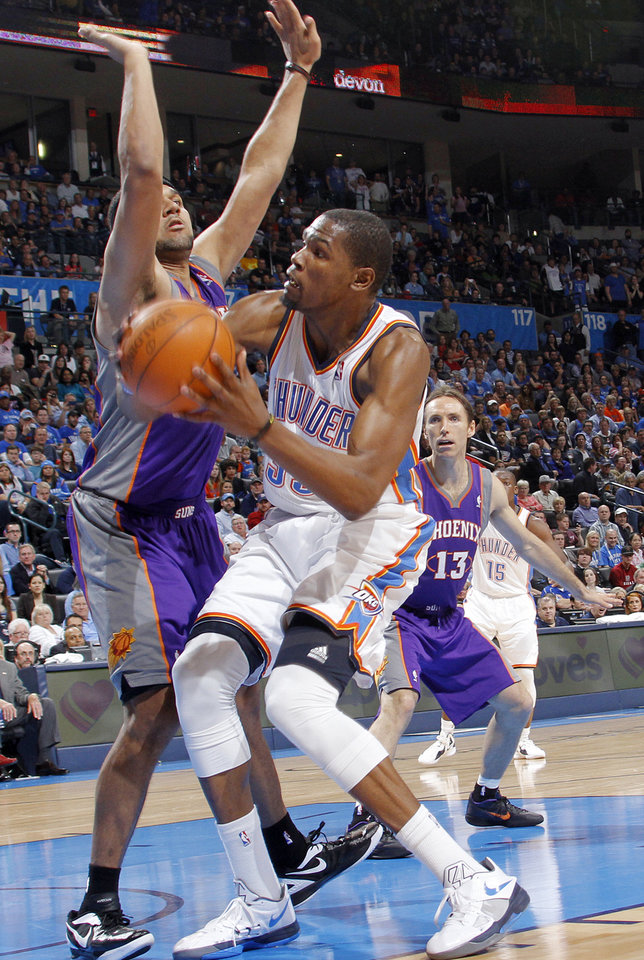 Photo - Oklahoma City Thunder small forward Kevin Durant (35) drives to the basket against Phoenix Suns small forward Jared Dudley (3) during the NBA basketball game between the Oklahoma City Thunder and the Phoenix Suns at the Chesapeake Energy Arena on Wednesday, March 7, 2012 in Oklahoma City, Okla.  Photo by Chris Landsberger, The Oklahoman