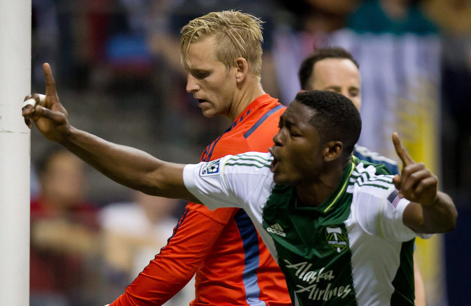 Photo - Vancouver Whitecaps goalkeeper David Ousted, left, of Denmark, stands nearby as Portland Timbers' Fanendo Adi, of Nigeria, celebrates a goal by teammate Alvas Powell during the second half of an MLS soccer game in Vancouver, British Columbia, on Saturday, Aug. 30, 2014. (AP Photo/The Canadian Press, Darryl Dyck)
