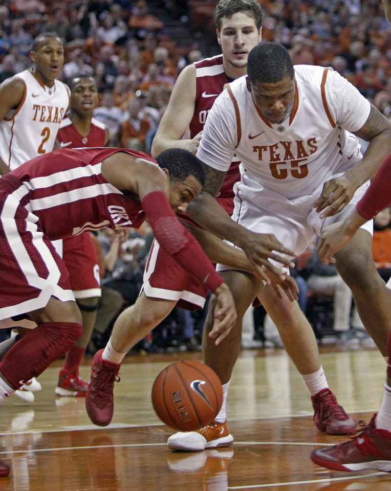 Photo - Oklahoma guard Jordan Woodard scrambles for the loose ball with Texas center Cameron Ridley (55) during the first half of an NCAA college basketball game, Saturday, Jan. 4, 2014, in Austin, Texas. (AP Photo/Michael Thomas)