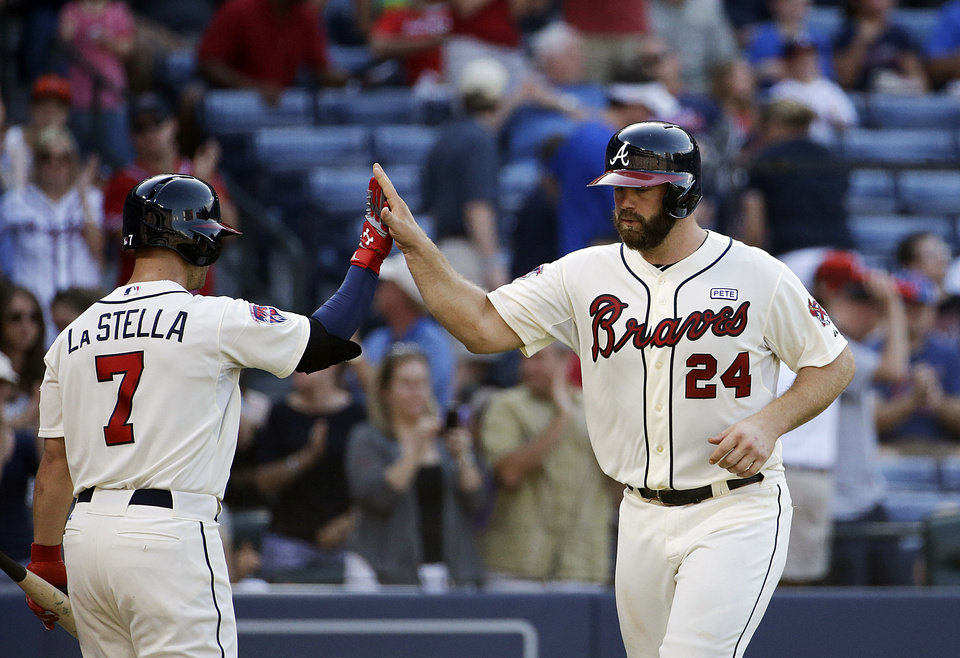 Photo - Atlanta Braves' Evan Gattis, right, high-fives teammate Tommy La Stella after hitting a home run in the second inning of a baseball game against the Miami Marlins, Sunday, Aug. 31, 2014, in Atlanta. (AP Photo/David Goldman)