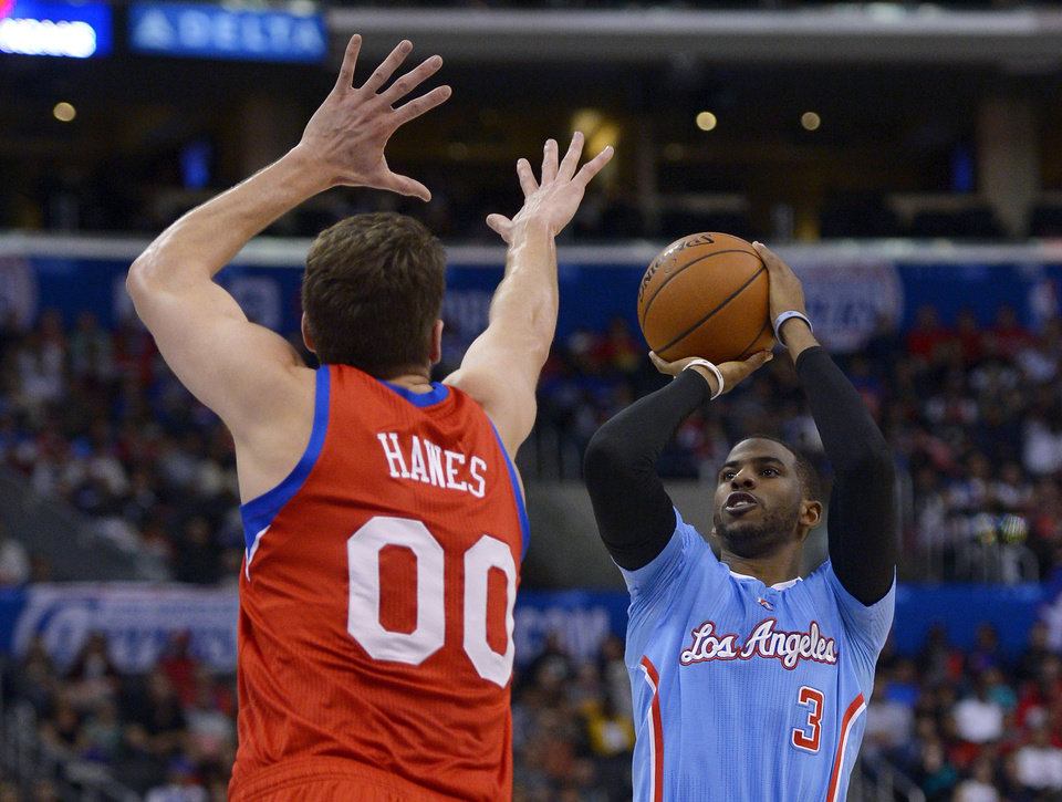 Photo - Los Angeles Clippers guard Chris Paul, right, puts up a shot as Philadelphia 76ers center Spencer Hawes defends during the first half of an NBA basketball game Sunday, Feb. 9, 2014, in Los Angeles. (AP Photo/Mark J. Terrill)