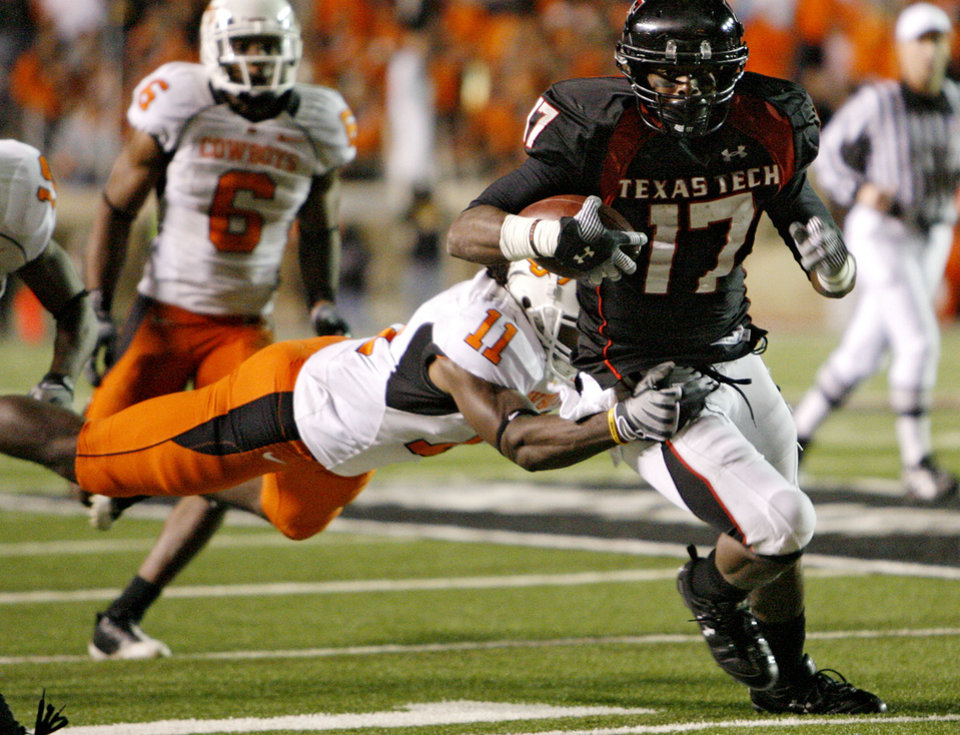 Photo - Oklahoma State's T.J. Bell (11) tries to make a diving tackel on Texas Tech's Detron Lewis (17) during the second half of the college football game between the Oklahoma State University Cowboys (OSU) and the Texas Tech Red Raiders at Jones AT&T Stadium on Saturday, Nov. 8, 2008, in Lubbock, Tex.BY CHRIS LANDSBERGER/THE OKLAHOMAN