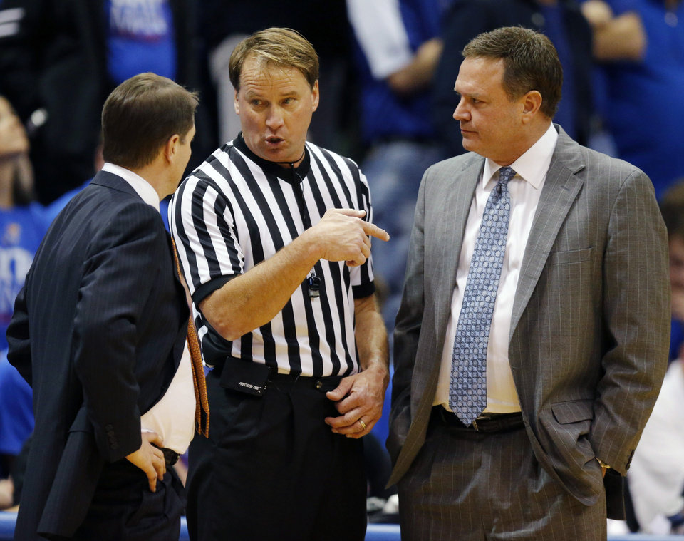 Photo - Referee John Higgins, center, explains a call to Oklahoma State head coach Travis Ford, left, and Kansas head coach Bill Self, right, during the first half of an NCAA college basketball game at Allen Fieldhouse in Lawrence, Kan., Saturday, Jan. 18, 2014. (AP Photo/Orlin Wagner)
