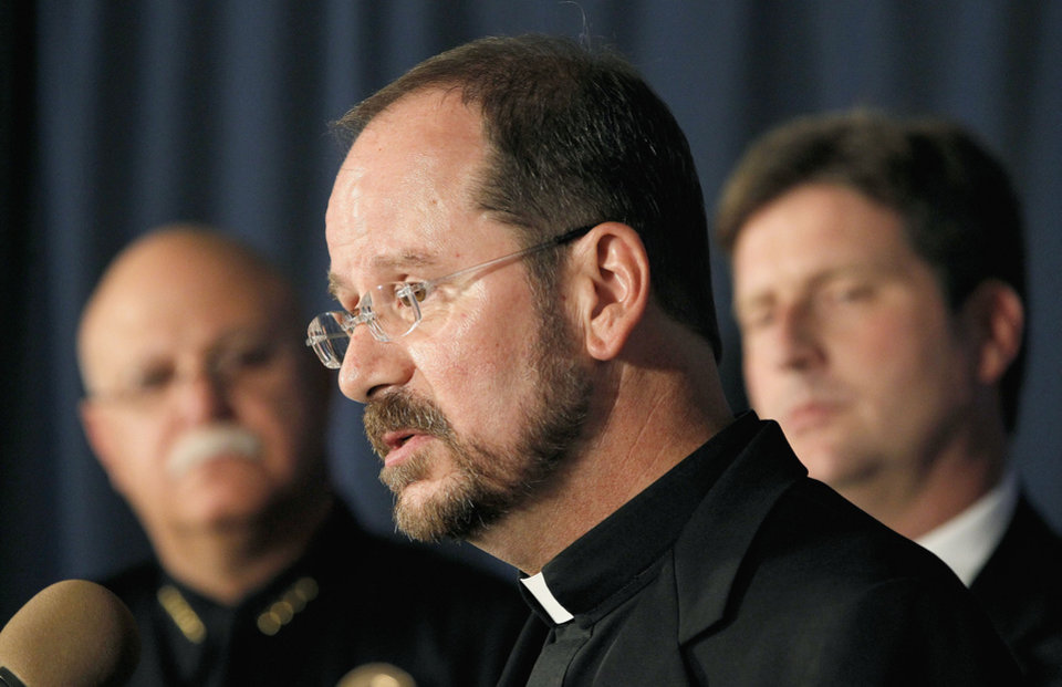 Photo - The Rev. Fred Adamson, middle, vicar general of the Phoenix Archdiocese, speaks at a news conference as Phoenix Chief of Police Daniel Garcia, left, and Phoenix Mayor Greg Stanton, right, listen in on Thursday, June 12, 2014, in Phoenix, after a Wednesday evening attack left priest, the Rev. Kenneth Walker, shot and killed and another priest, the Rev. Joseph Terra, critically injured at the Roman Catholic church the Mother of Mercy Mission.  Police have no suspects at this point, but they are canvassing the neighborhood and going over physical evidence from the scene. (AP Photo/Ross D. Franklin)