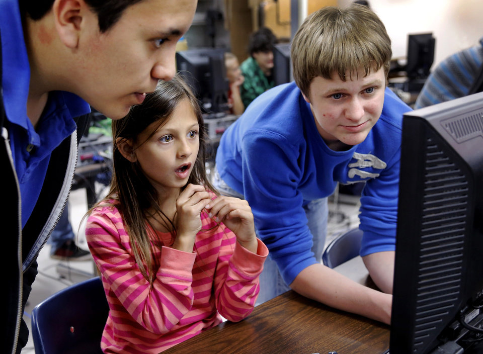 Photo - Second grader Charity Fristad's expression displays her amazement as she watches the computer screen with help from eighth grade students Javier Ramirez, left, and Nathan Day.  stares at a computer screen as three junior high students gather around to help her. Moore Central Junior High students who are enrolled in video game design classes have created math and language learning games using characters from books their neighbors from Plaza Towers Elementary love to read. Students from both schools will get together on Wednesday, May 14, 2014, to play the games and get an opportunity to experience writing CODE.    Photo by Jim Beckel, The Oklahoman