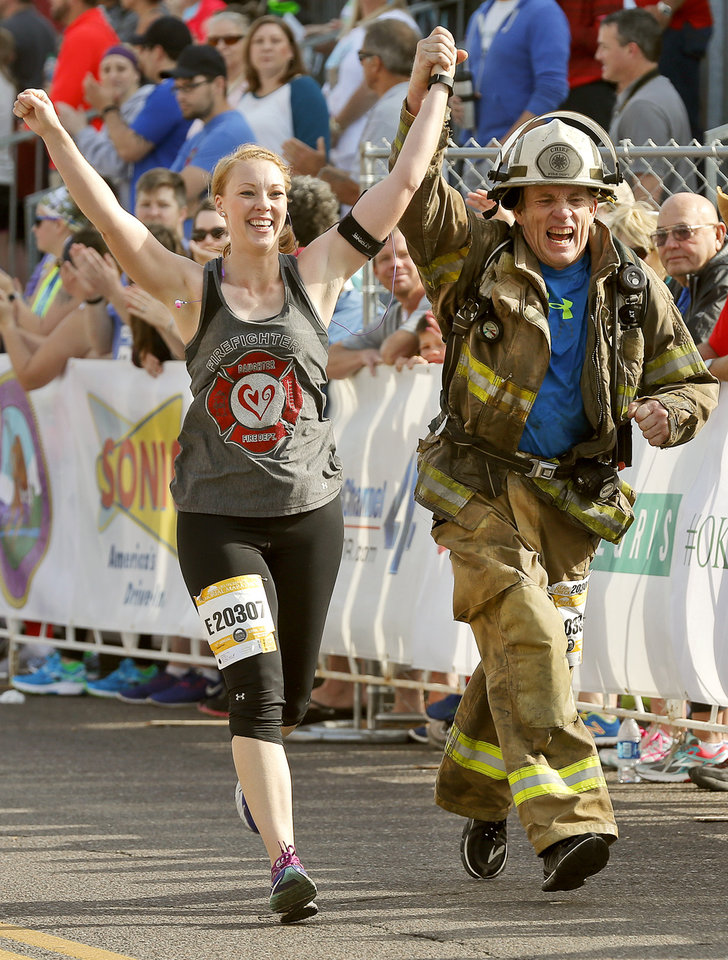 Photo - Julie Hayes and fire chief Jon Pickel celebrate finishing the half marathon during the Oklahoma Memorial Marathon in Oklahoma City, Okla. on Sunday, April 24, 2016.   Photo by Chris Landsberger, The Oklahoman