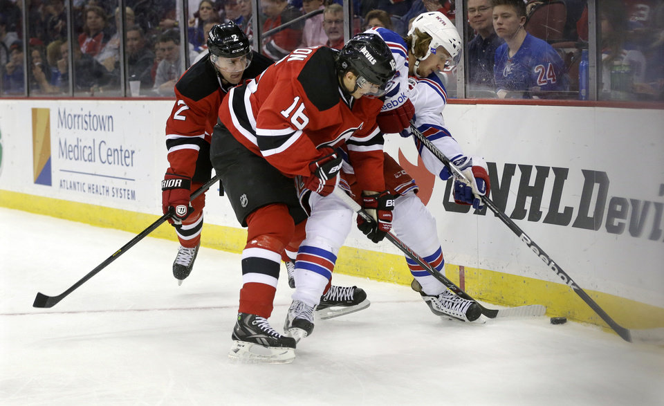 Photo - New York Rangers' Carl Hagelin, of Sweden, tries to control the puck as New Jersey Devils' Jacob Josefson (16), of Sweden, and Marek Zidlicky, of the Czech Republic, try to make a steal during the first period of an NHL hockey game game Saturday, March 22, 2014, in Newark, N.J. (AP Photo/Mel Evans)