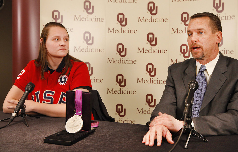 Photo - Paralympic silver medalist Monique Burkland listens as orthopedic surgeon William Ertl speaks at a news conference at The Children's Hospital at OU Medical Center on Tuesday. Photos By David McDaniel, The Oklahoman