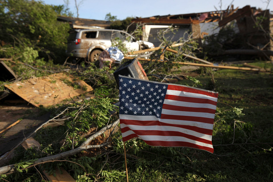 Photo - An American flag blows in the wind outside a home that was struck by a tornado in Woodward, Okla., on April 15, 2012.  BRYAN TERRY - THE OKLAHOMAN ARCHIVES