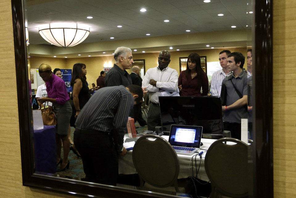 Photo - Robert Orkin of the company TxT-Alert, third from left, talks with job seekers Sept. 17 during a job fair held by National Career Fairs in Fort Lauderdale, Fla. AP Photo