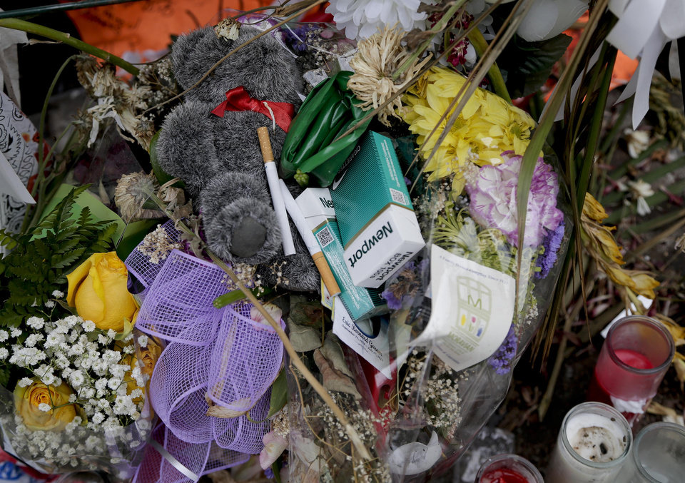 Photo - Candles, flowers, stuffed animals and cigarettes lay at a makeshift memorial for Eric Garner, Friday, Aug. 1, 2014, in the Staten Island borough of New York. Garner died after he was put in a chokehold while being arrested last month for selling untaxed loose cigarettes. On Friday, the medical examiner ruled Garner's death to be a homicide caused by a police chokehold. (AP Photo/Julie Jacobson)