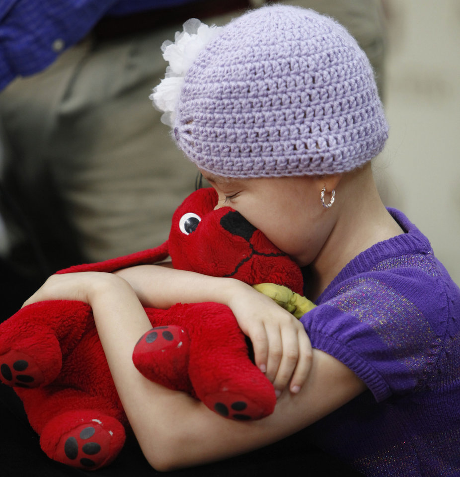 8-year-old Sheridian Bautista hugs her stuffed dog as her doctors explain a new implant procedure used after doctors removed a large tumor from Sheridian\'s leg at Children\'s Hospital at OU Medical Center in Oklahoma City , Tuesday, September 20, 2011. Photo by Steve Gooch