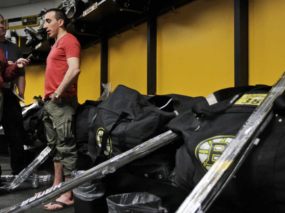 Photo -   Equipment bags are packed in the Boston Bruins' locker room as left wing Brad Marchand speaks to reporters at TD Garden in Boston, Friday, April 27, 2012, about their loss to the Washington Capitals in Game 7 and the Bruins' elimination from the Stanley Cup hockey playoffs. (AP Photo/Elise Amendola)