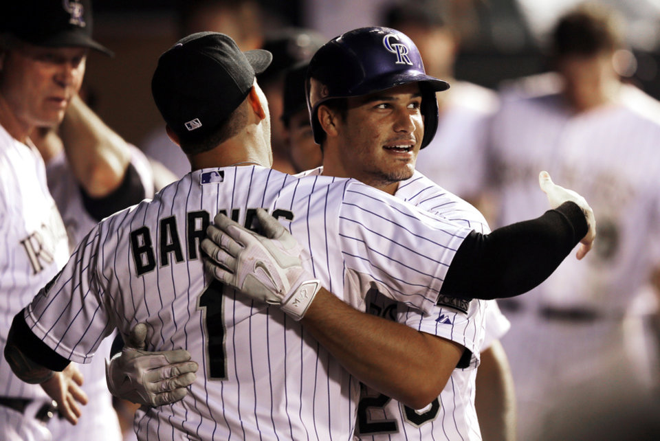 Photo - Colorado Rockies' Nolan Arenado, right, hugs Brandon Barnes after hitting a solo home run off Kansas City Royals starting pitcher James Shields during the fifth inning of a baseball game Tuesday, Aug. 19, 2014, in Denver. (AP Photo/Jack Dempsey)