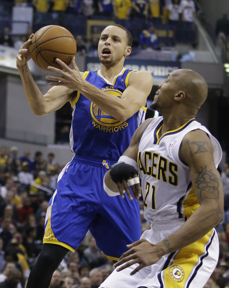 Photo - Golden State Warriors' Stephen Curry, left, shoots against Indiana Pacers' David West (21) during the first half of an NBA basketball game Tuesday, March 4, 2014, in Indianapolis. (AP Photo/Darron Cummings)