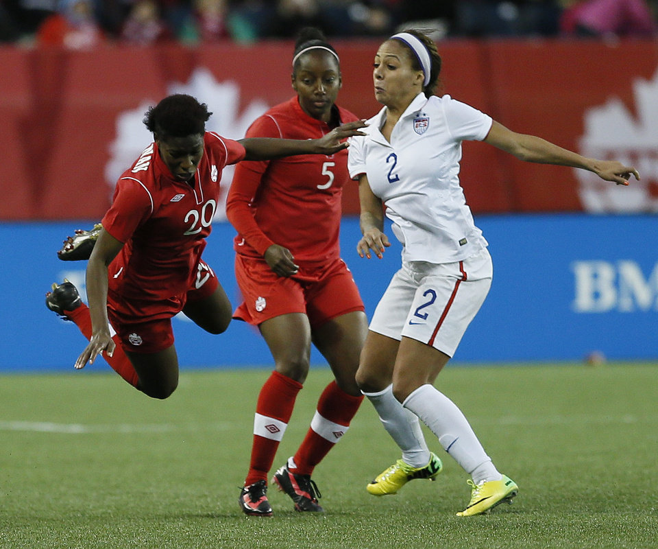 Photo - Canada's defender Robyn Gayle (5) looks on as Kadeisha Buchanan (20) is fouled by USA's forward Sydney Leroux (2) during second half soccer action during a friendly match in Winnipeg, Manitoba, Thursday, May 8, 2014. (AP Photo/The Canadian Press, John Woods)