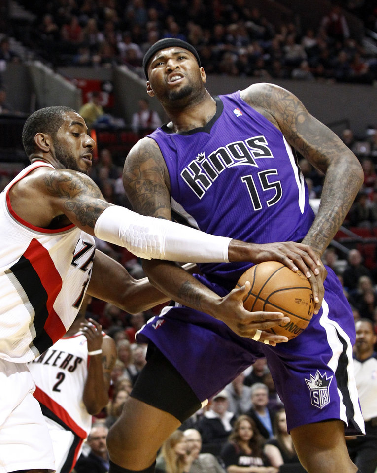 Photo - Portland Trail Blazers forward LaMarcus Aldridge, left, reaches in and fouls Sacramento Kings center DeMarcus Cousins during the first quarter of their NBA basketball game in Portland, Ore., Saturday, Dec. 8, 2012.(AP Photo/Don Ryan)