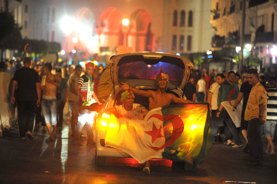 Photo - In this photo dated Thursday, June 26, 2014, Algerian soccer fans celebrate in the streets of Algiers, Algeria, after their team qualified for round of 16 following the Group H World Cup soccer match between Algeria and Russia. Algeria drew with Russia 1-1, and advanced to the round of 16 for the first time in their World Cup history. (AP Photo/Sidali Djarboub)