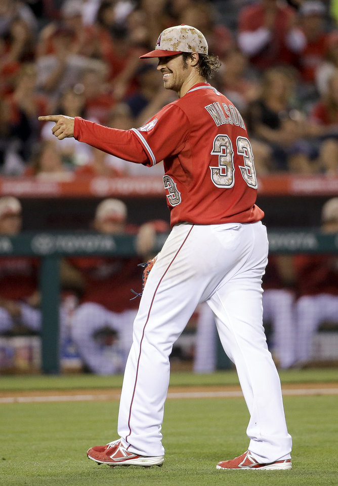 Photo - Los Angeles Angels starting pitcher C.J. Wilson celebrates the end of the top of the eighth inning of a baseball game against the Tampa Bay Rays in Anaheim, Calif., Saturday, May 17, 2014. (AP Photo/Chris Carlson)