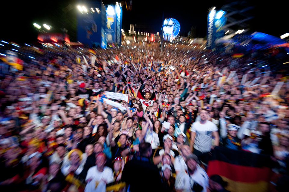 Photo - In this zoomed picture, German soccer fans react after  Germany won  the final match   of  the Brazil World Cup 2014 between Germany and Argentina played  in Rio de Janeiro, Brazil, at a public viewing  area  called 'Fan Mile' in Berlin, Sunday, July 13, 2014.  Germany won by 1-0.  (AP Photo/Steffi Loos)