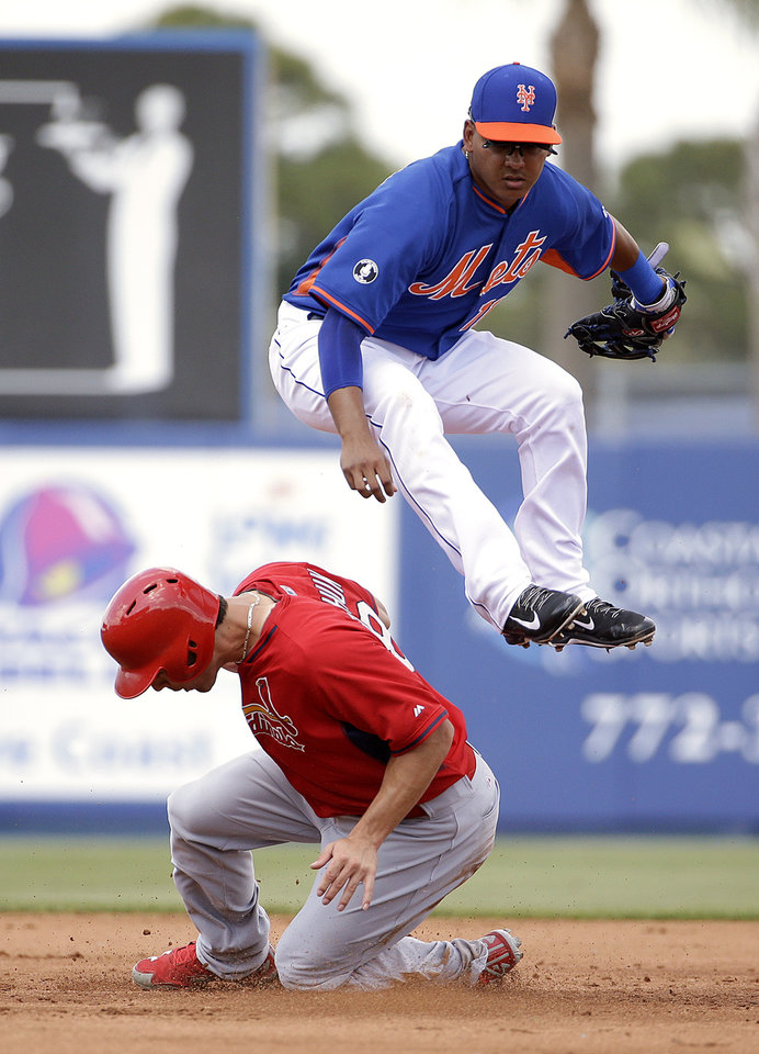 Photo - New York Mets shortstop Ruben Tejada, top, jumps over St. Louis Cardinals' Randal Grichuk after throwing to first base for a double play in the second inning of an exhibition spring training baseball game, Wednesday, March 12, 2014, in Port St. Lucie, Fla. (AP Photo/David Goldman)