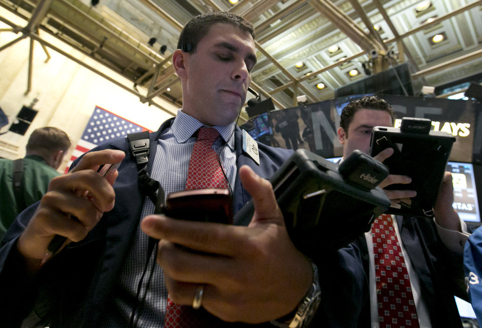 Photo - Trader Craig Spector, left, works on the floor of the New York Stock Exchange Wednesday, Aug. 6, 2014. U.S. stocks are little changed in early trading Wednesday as investors worry about escalating tensions between Russia and the Ukraine. Investors were also holding back after two larger merger bids were pulled. (AP Photo/Richard Drew)