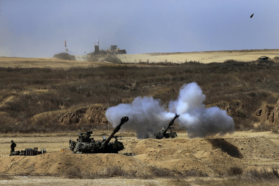Photo - An Israeli tank fires towards Gaza, near the Israel and Gaza border in the morning of Sunday, July 27, 2014. Hamas on Sunday agreed to observe a 24-hour truce in Gaza after initially rejecting a similar Israeli offer, as fighting resumed and the two sides wrangled over the terms of a lull that international diplomats had hoped could be expanded into a more sustainable truce. Hamas spokesman Sami Abu Zuhri said the truce would go into effect at 2 p.m. (1100 GMT) Sunday. But shortly after the truce was to have started warning sirens wailed in southern Israel and the military said three rockets landed in the area, without causing casualties or damage. (AP Photo/Tsafrir Abayov)