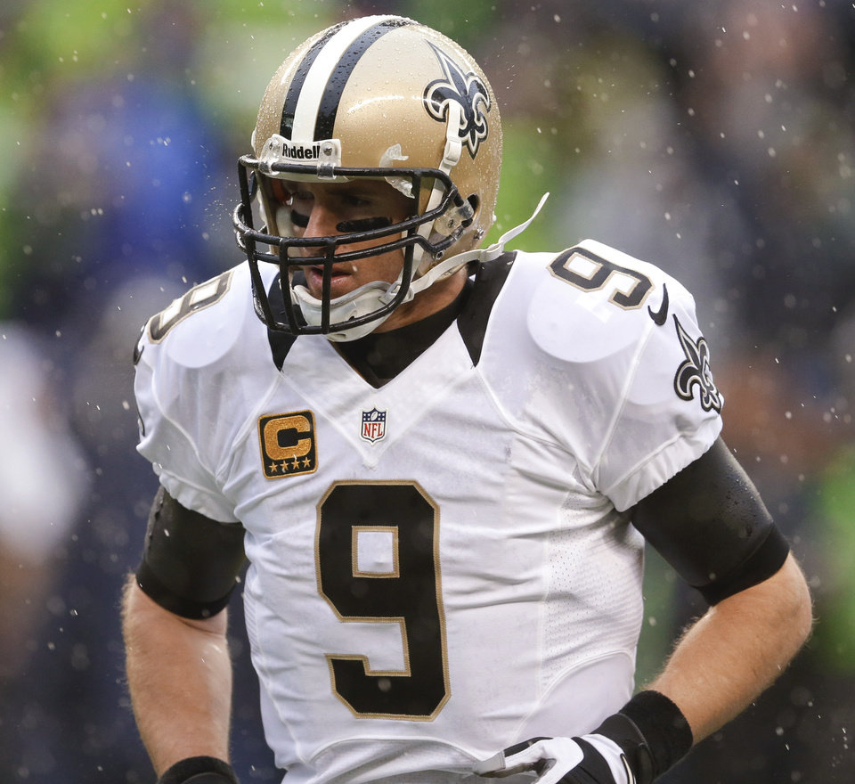 Photo - New Orleans Saints quarterback Drew Brees runs off the field during the second quarter of an NFC divisional playoff NFL football game against the Seattle Seahawks in Seattle, Saturday, Jan. 11, 2014. (AP Photo/Ted S. Warren)
