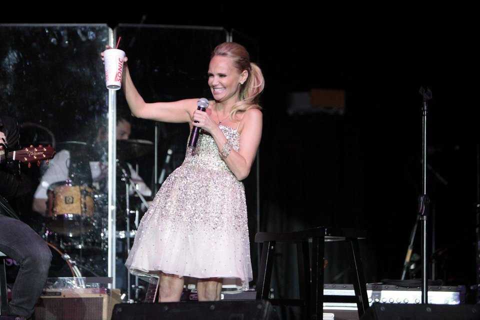 Photo - Kristin Chenoweth thanks someone from the crowd fir giving her a Sonic drink during her performance at the 2011 Oklahoma Music Hall of Fame. Photo by Jay Spear