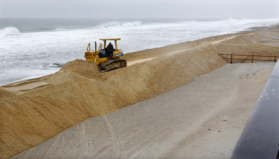 Photo - A worker uses a bulldozer to spread sand Wednesday, Nov. 7, 2012, in Harvey Cedars, on Long Beach Island N.J. A nor'easter smacked the storm-ravaged Jersey shore on Wednesday, a week and half after Superstorm Sandy wrecked many of its beaches, dunes and boardwalks, and left low-lying communities newly vulnerable to flooding, wind damage and power outages. Public works crews up and down the shore were using bulldozers, front-end loaders and earth movers to push tons of sand back onto what was left of the beaches.  (AP Photo/Mel Evans) (AP Photo/Mel Evans) ORG XMIT: NJME105