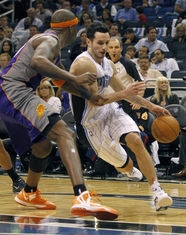Orlando Magic guard J.J. Redick, right, drives around Phoenix Suns center Jermaine O'Neal during the first half of an NBA basketball game in Orlando, Fla., on Sunday, Nov. 4, 2012. (AP Photo/Reinhold Matay)