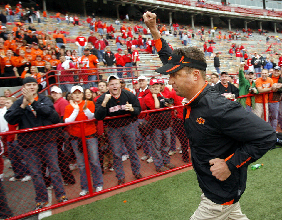 Photo - OSU head coach Mike Gundy runs off the field with his fist held up after the college football game between Oklahoma State University (OSU) and the University of Nebraska (NU) at Memorial Stadium in Lincoln, Neb., Saturday, October 13, 2007. OSU won, 45-14. By Nate Billings, The Oklahoman