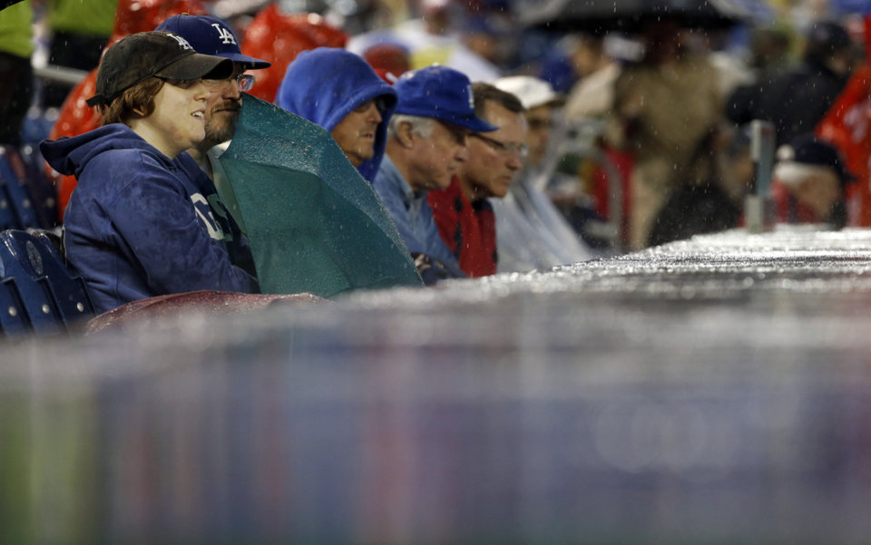 Photo - Fans sit in the rain during the second inning of a baseball game between the Los Angeles Dodgers and the Washington Nationals at Nationals Park, Monday, May 5, 2014, in Washington. (AP Photo/Alex Brandon)