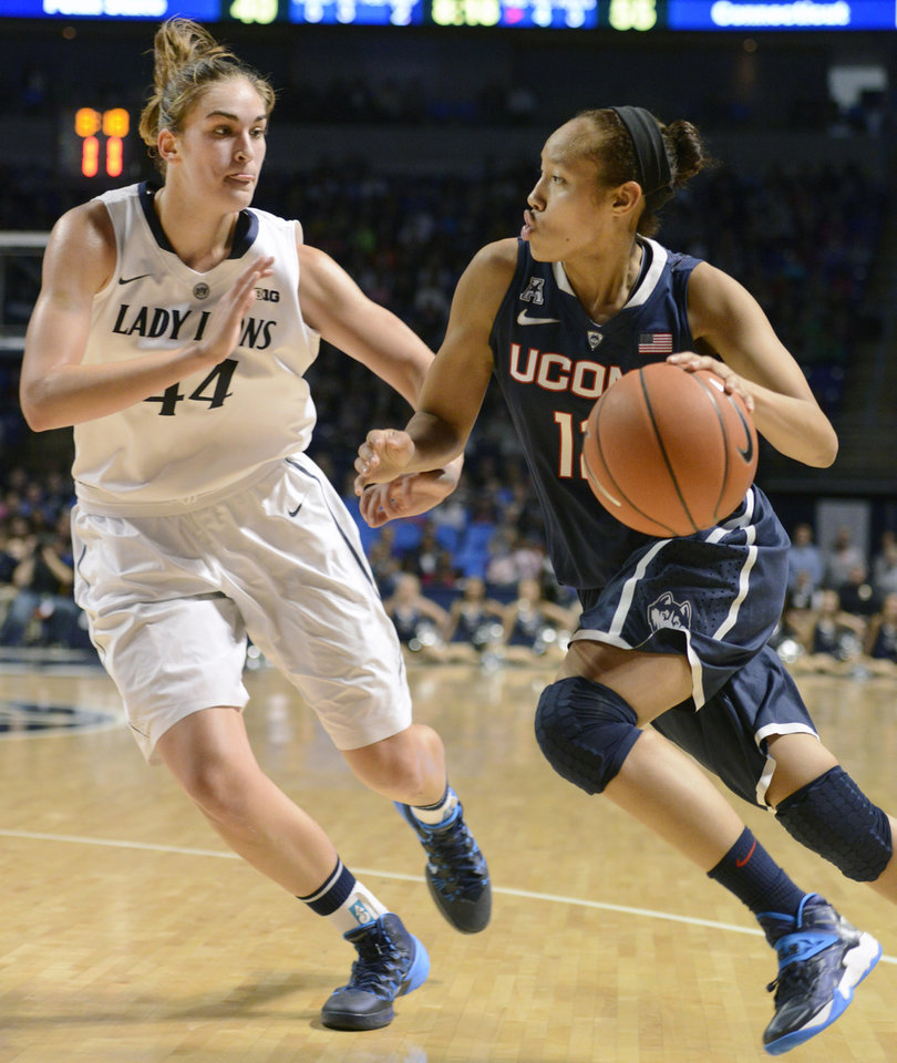 Photo - Connecticut's Saniya Chong (12) dribbles past Penn State's Tori Waldner (44) in the second half of an NCAA college basketball game on Sunday, Nov. 17, 2013, in State College, Pa. Connecticut won 71-52. (AP Photo/John Beale)