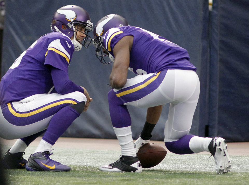 Photo - Minnesota Vikings quarterback Matt Cassel, left, celebrates with teammate Greg Jennings after Jennings' 57-yard touchdown reception during the first half of an NFL football game against the Philadelphia Eagles, Sunday, Dec. 15, 2013, in Minneapolis. (AP Photo/Andy King)
