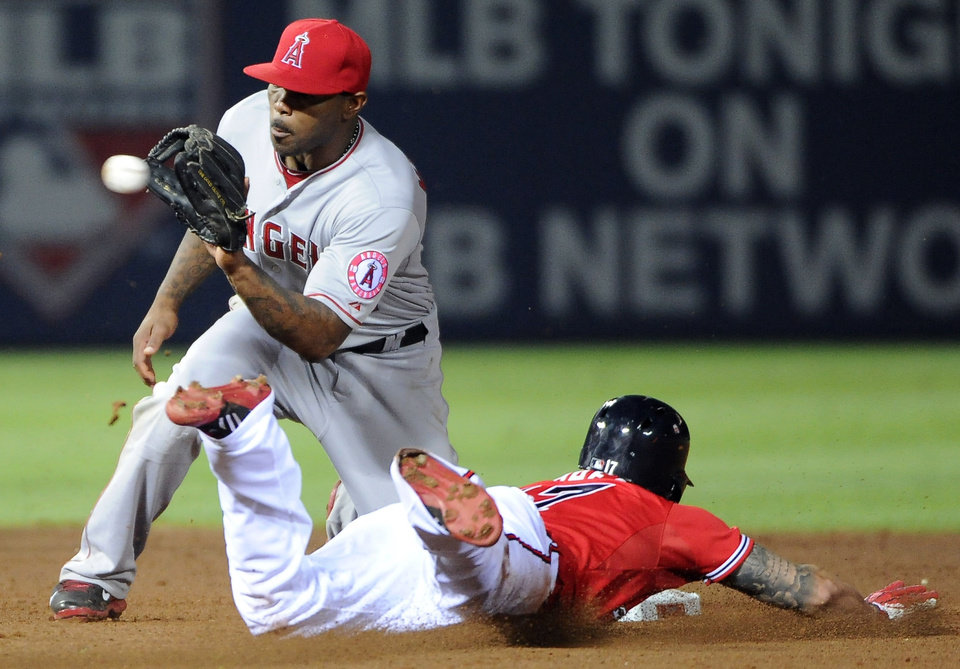 Photo - Atlanta Braves' Jordan Schafer (17) beats the throw and steals second base behind Los Angeles Angels' Howie Kendrick, left, during the seventh inning of a baseball game on Friday, June 13, 2014, in Atlanta. (AP Photo/David Tulis)