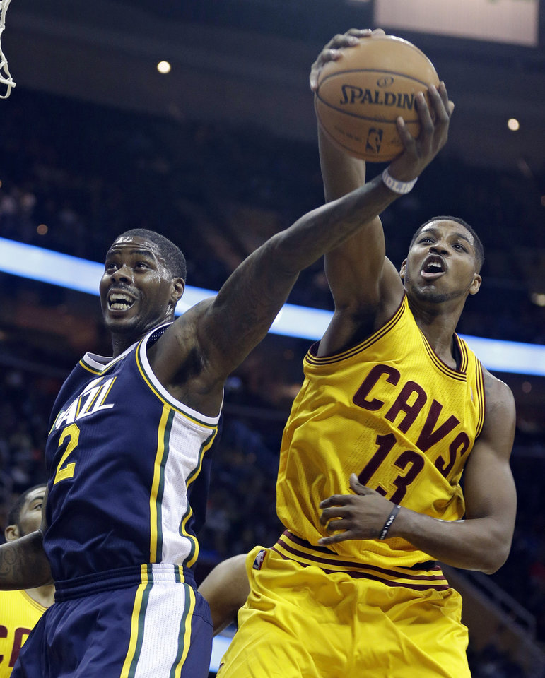 Photo - Utah Jazz's Marvin Williams (2) and Cleveland Cavaliers' Tristan Thompson (13), from Canada, battle for a rebound during the first quarter of an NBA basketball game on Friday, Feb. 28, 2014, in Cleveland. (AP Photo/Tony Dejak)