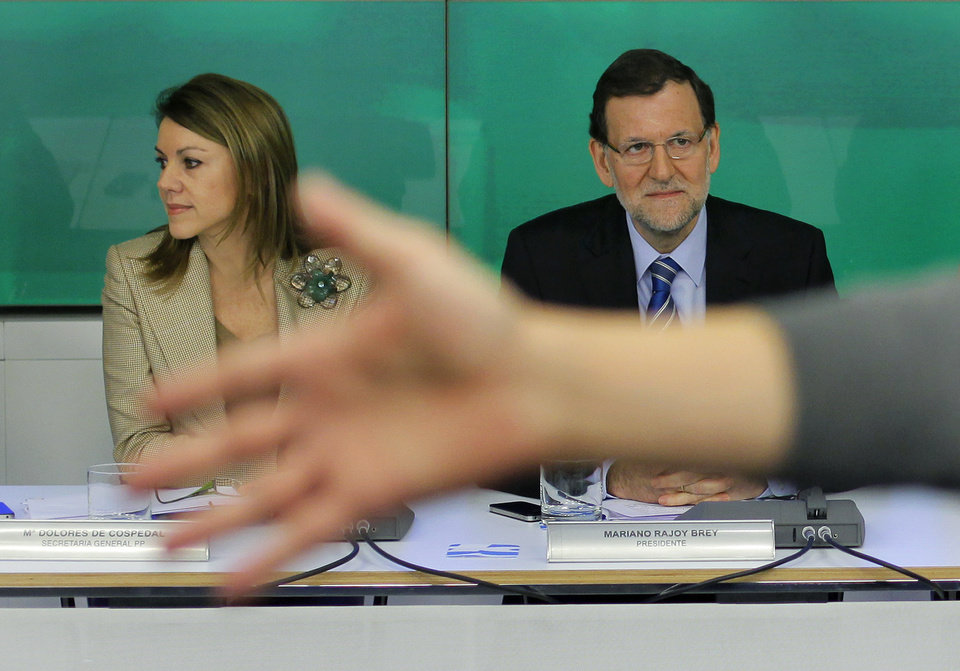 Photo - Spain's Prime Minister Mariano Rajoy, right, and Popular Party's General Secretary, Dolores Cospedal, left, sit as a member of the Party gestures for the press to leave prior to an emergency meeting at the Popular Party headquarter in Madrid, Spain, Saturday, Feb. 2, 2013. Spain's governing Popular Party insists its financial accounts are totally legal and denies a newspaper report of regular under-the-table payments to leading members, including current Prime Minister Mariano Rajoy. The scandal first broke when after the National Court reported that former party treasurer Luis Barcenas amassed an unexplained euro 22 million ($30 million) in a Swiss bank account several years ago. In a statement Thursday Jan. 31, 2013, the party denied the existence of