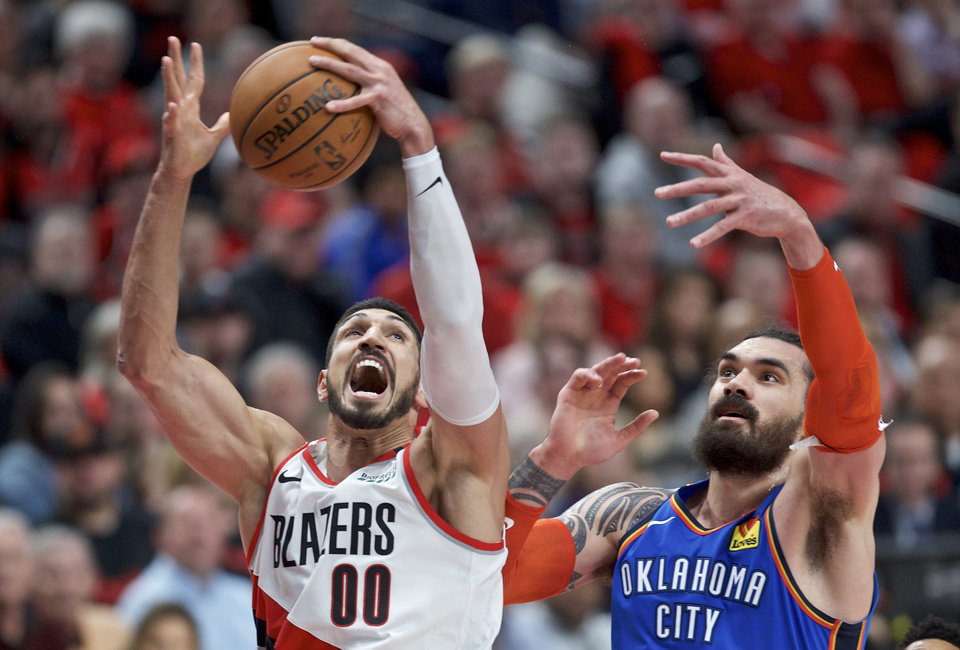 Photo - Portland Trail Blazers center Enes Kanter, left, rebounds the ball next to Oklahoma City Thunder center Steven Adams during the first half of Game 2 of an NBA basketball first-round playoff series Tuesday, April 16, 2019, in Portland, Ore. (AP Photo/Craig Mitchelldyer)